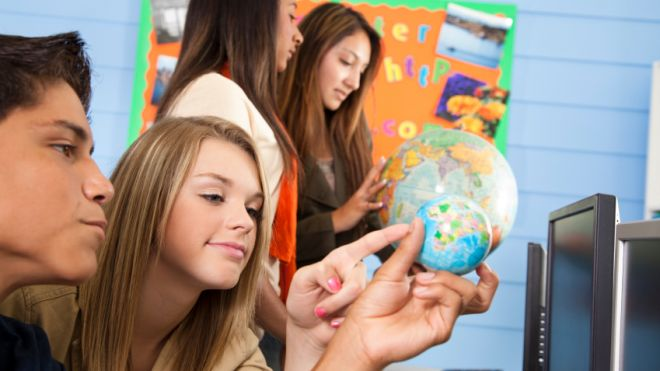 High-school-students-look-at-globe-and-learn-in-classroom-education